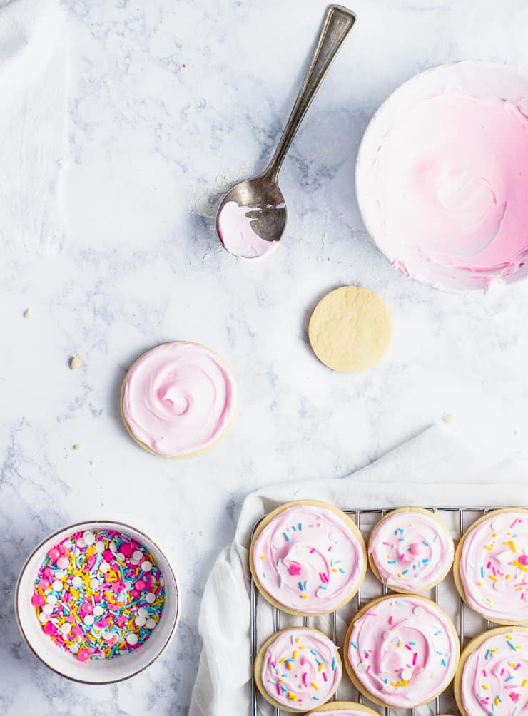 frosted sugar cookies on a cooling rack with sprinkles and bowl of frosting in the background