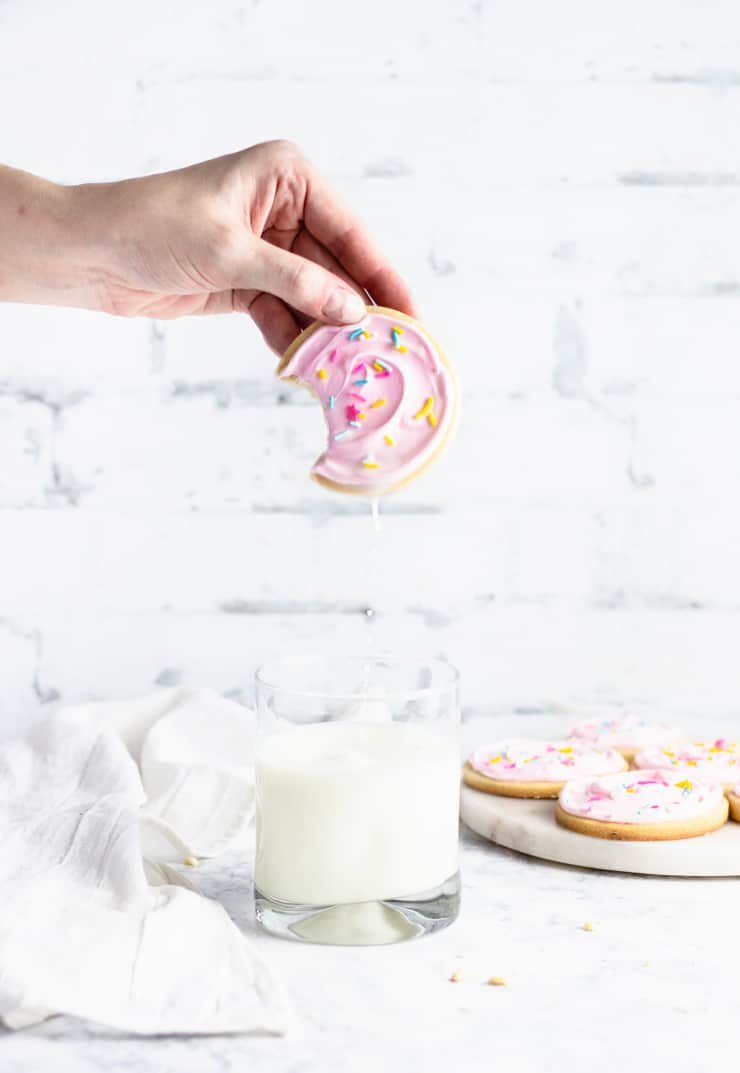 half-eaten sugar cookie being dunked in a glass of milk