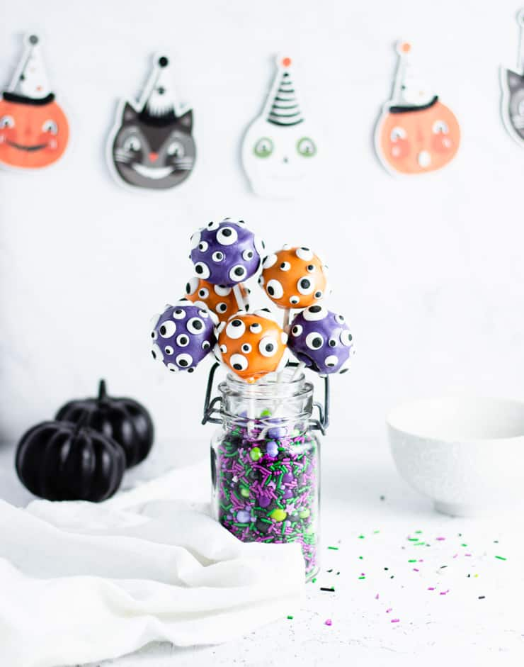 straight on shot of cake pops in a jar with halloween decorations in the background
