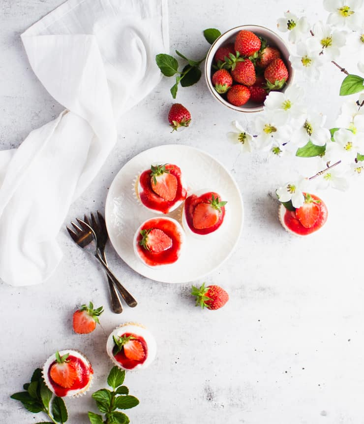 a plate of strawberry shortcake cupcakes next to a bowl of strawberries, flowers and silverware