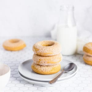 stack of doughnuts in front of a jug of milk