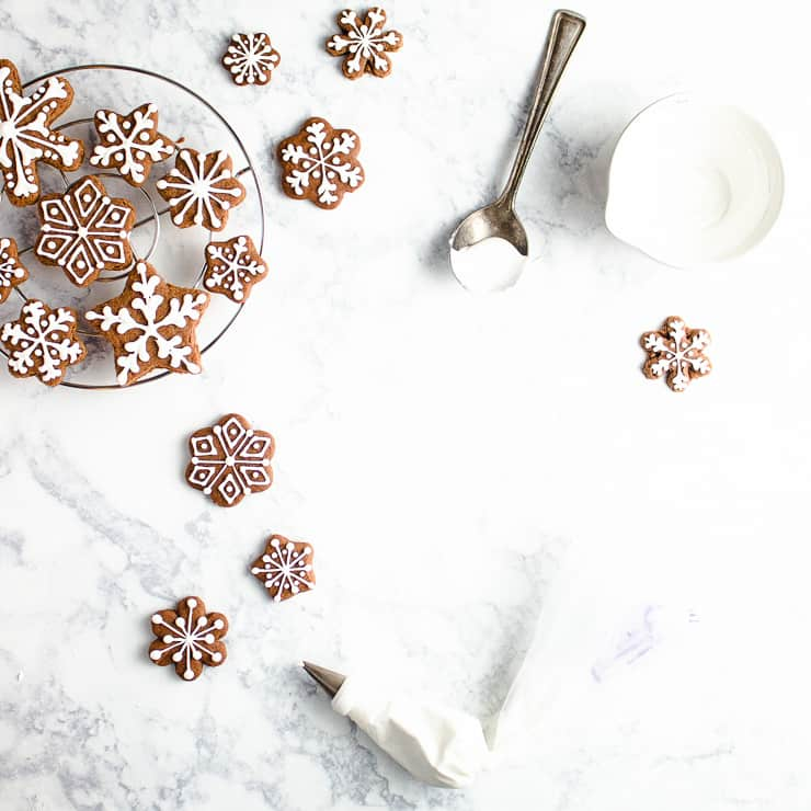 iced gingerbread cookies with an empty bowl of icing and a spoon