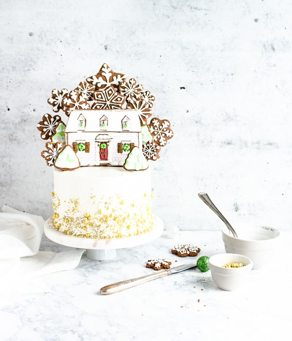 cake with gold sprinkles and gingerbread cookies on top