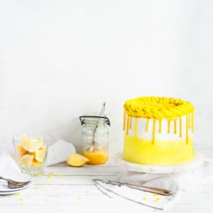 cake with a jar of lemons and lemon curd in the background
