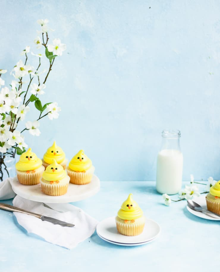 Chick cupcake on a plate with a platter of cupcakes, a vase of flowers and a bottle of milk in the background