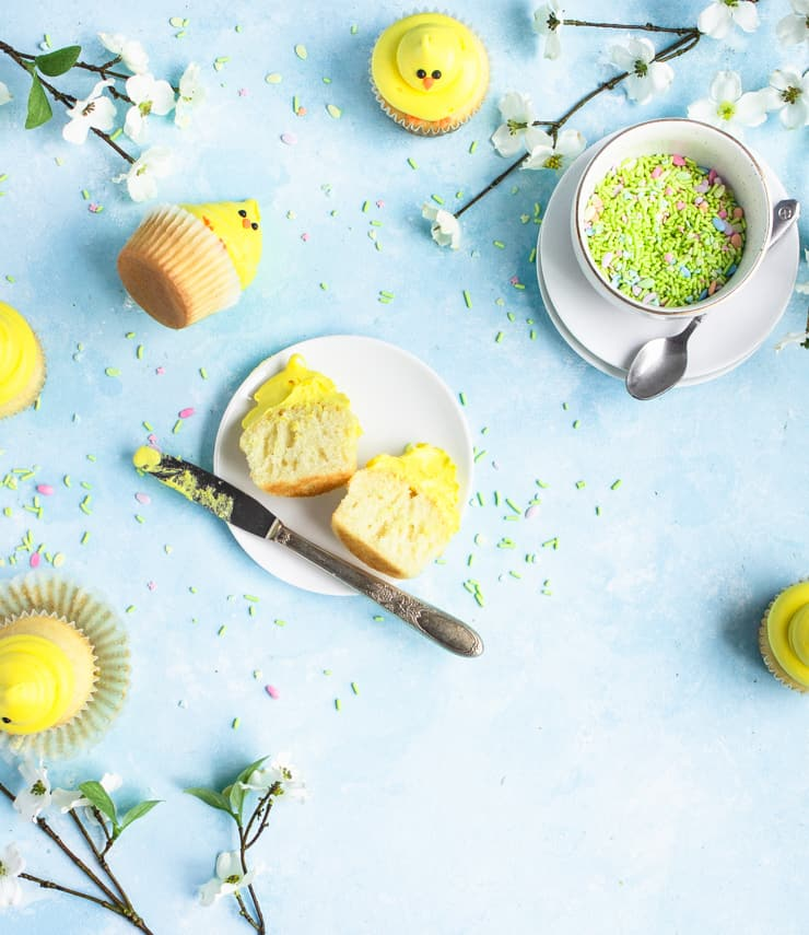 A cupcake is cut in half on a plate with cupcakes, sprinkles and flowers strewn around a blue backdrop.