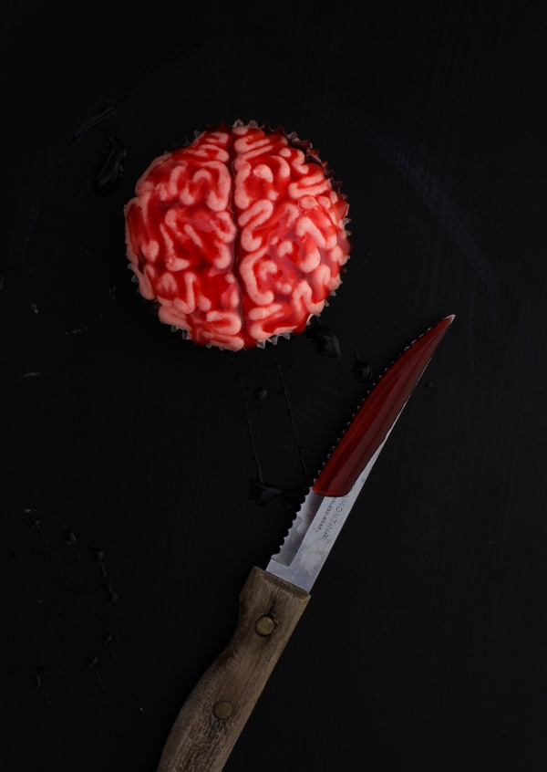 bleeding brain cupcake against a black backdrop with a bloody knife to the side