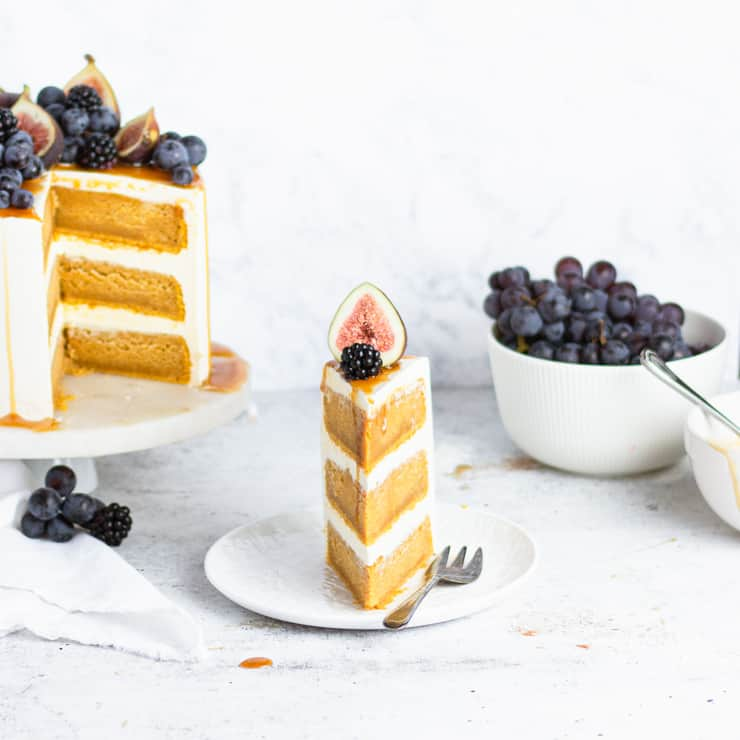 slice of cake next to cake and a bowl of grapes