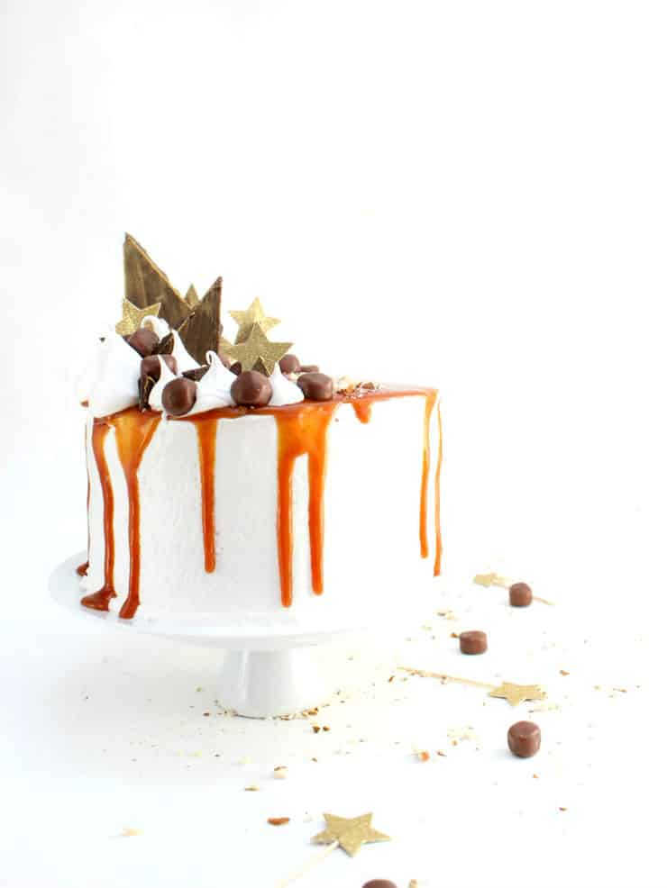 This cake is a sweet take on the classic Thanksgiving sweet potato casserole combining layers of moist sweet potato cake, decadent marshmallow frosting, and topped with caramel and chocolates! | The Simple, Sweet Life