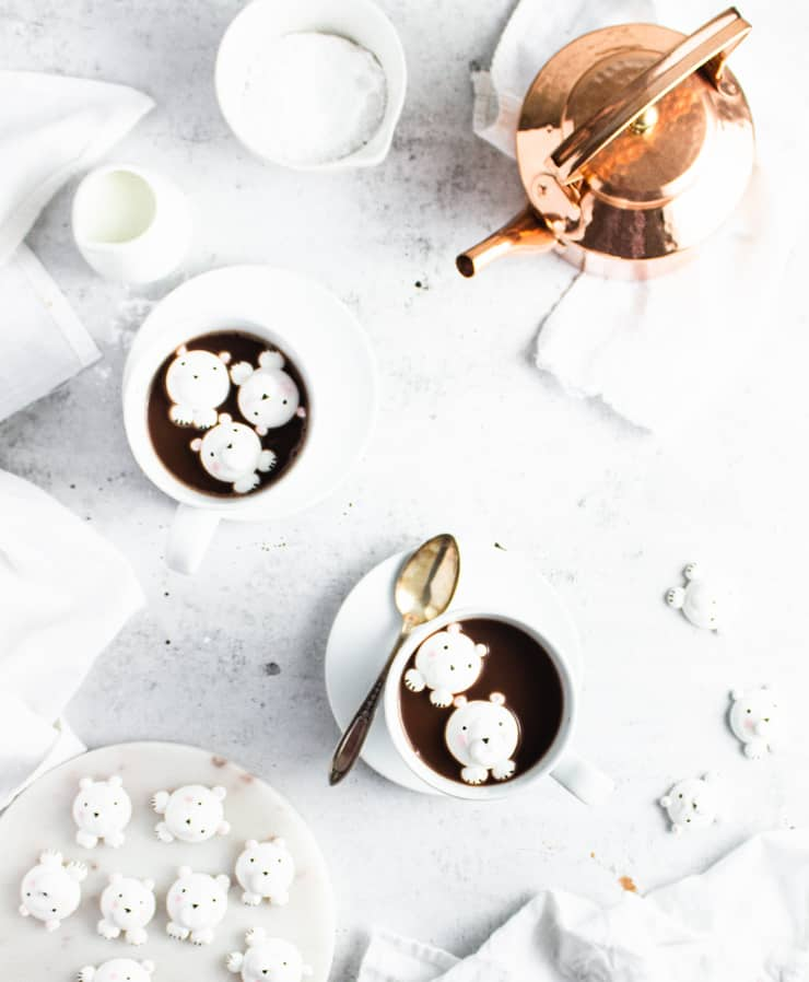 two cups of hot chocolate on saucers with a bronze kettle and marshmallows