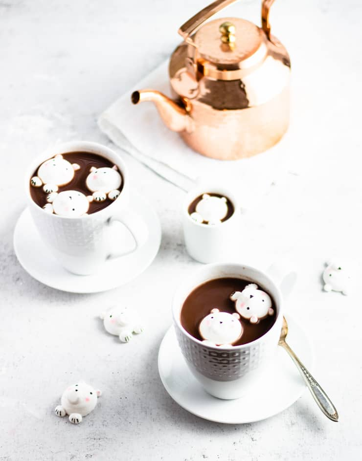two cups of hot chocolate with polar bear marshmallows floating in them