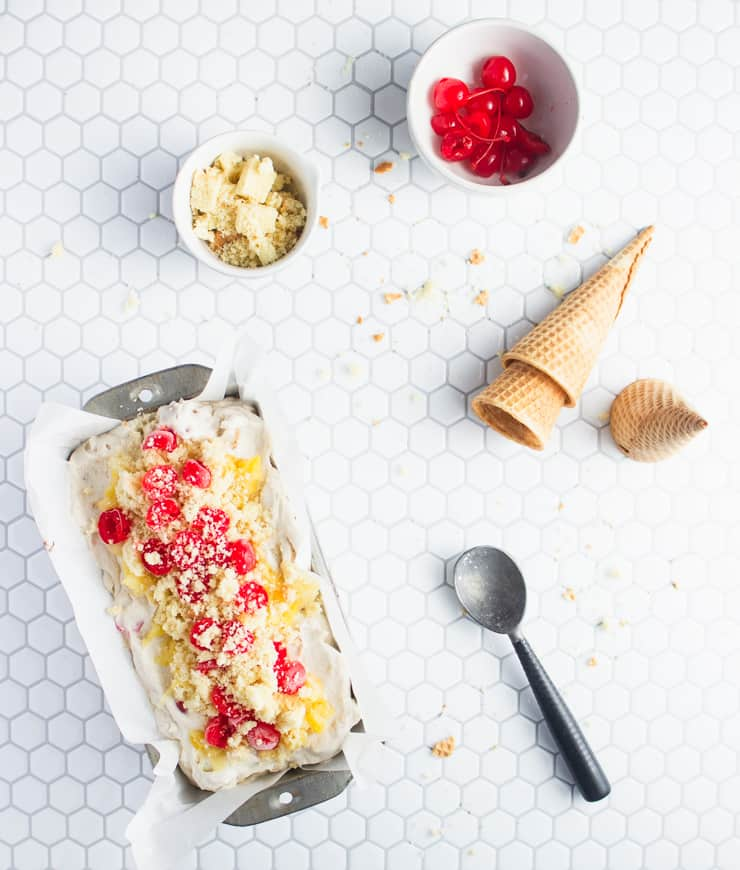 ice cream in a pan with cherries, pineapple and cones nearby