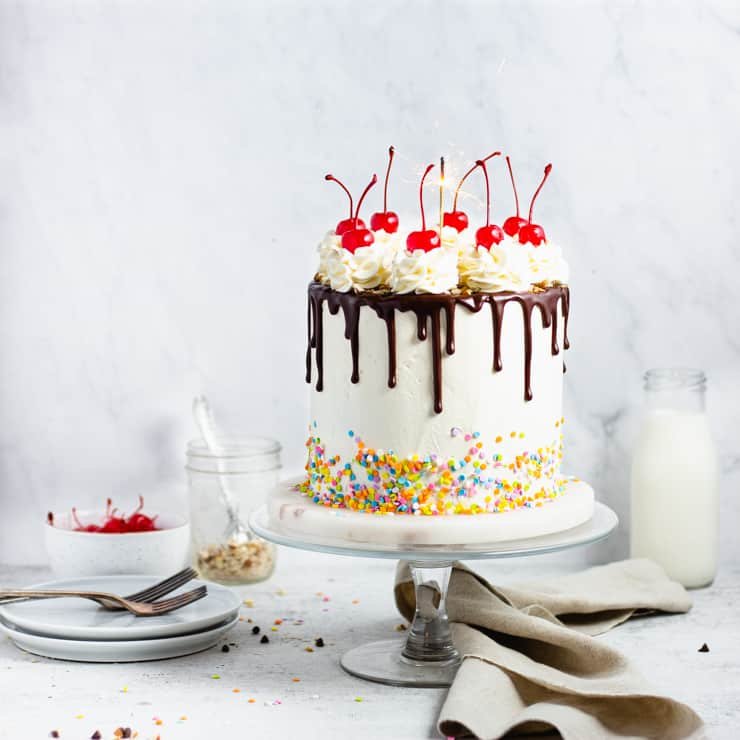 fudge cake with a chocolate drip, cherries and sprinkles with a sparkler on top