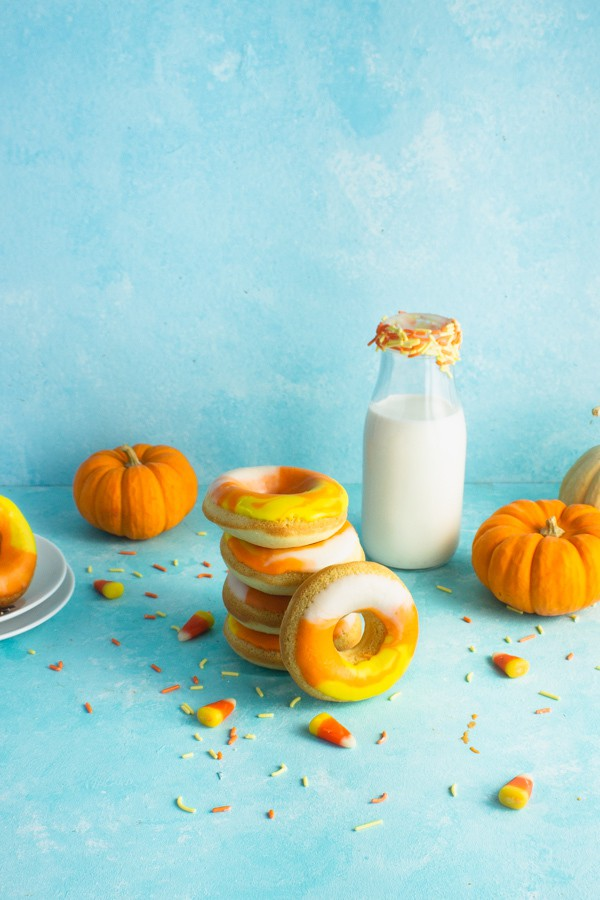a stack of candy corn doughnuts in front of a jug of milk with doughnuts and pumpkins in the background