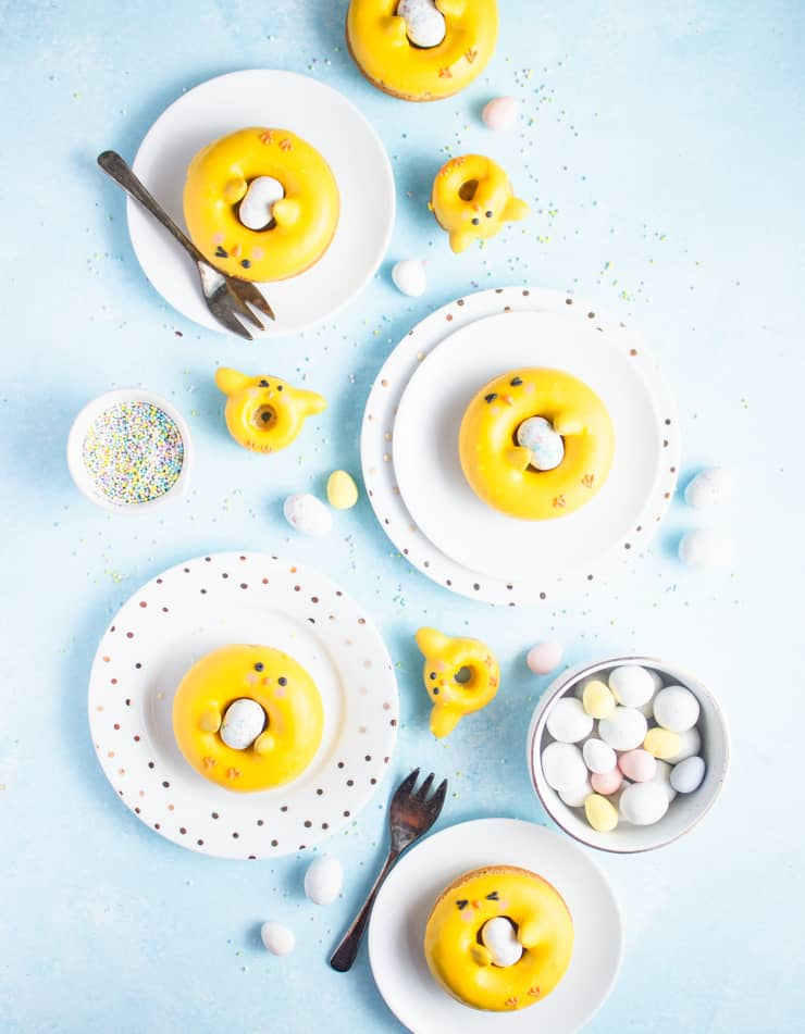 Plates of various sizes with donuts decorated to look like chicks holding candy easter eggs