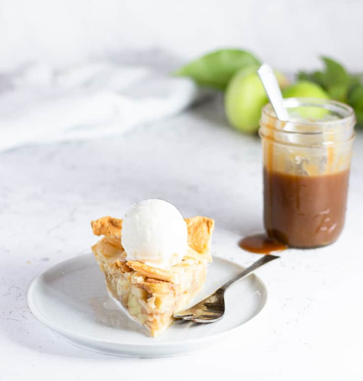 slice of apple pie in front of jar of butterscotch