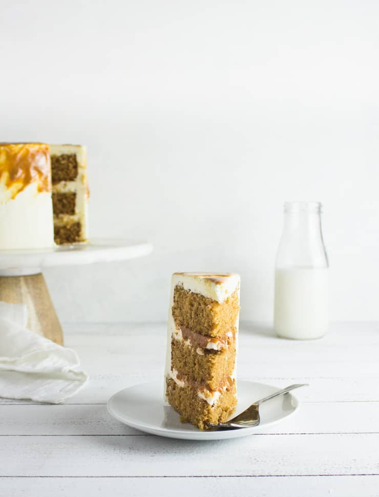 Slice of espresso cake against a white backdrop with cake and a pitcher of milk in the background