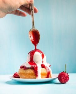 Fresh strawberry syrup dripping onto an ice cream topped doughnut