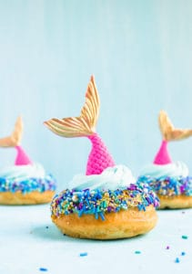 Three pink and gold mermaid tails on top of doughnuts with blue, purple and gold sprinkles