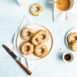 Plate of doughnuts on a white napkin with a knife, jar of milk and bowl of glaze around it