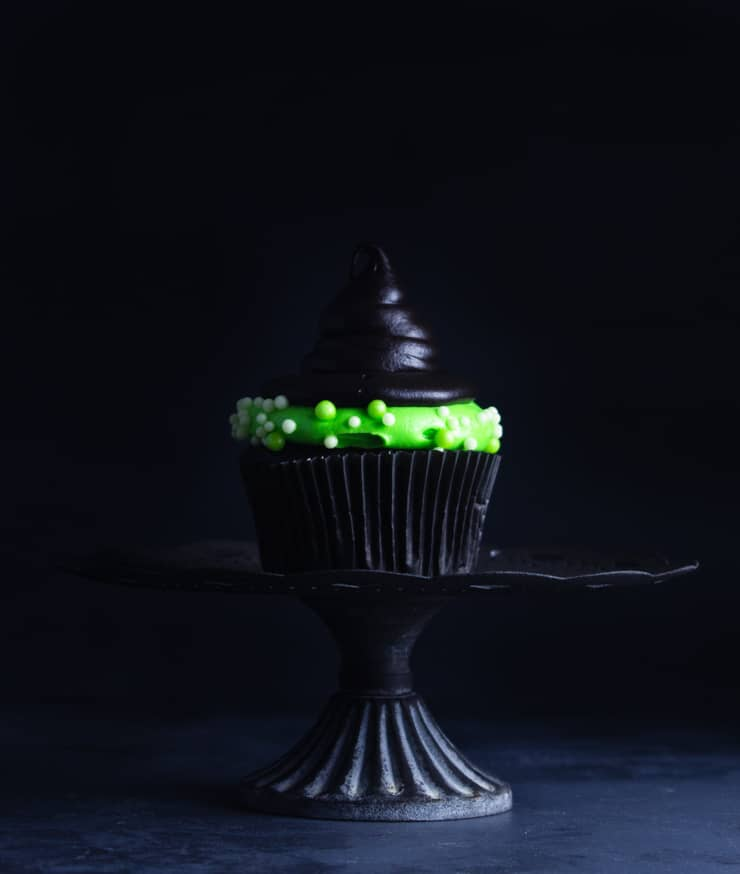 one witch hat cupcake on a black cake stand against a black backdrop