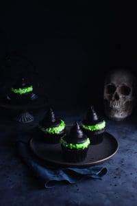 three witch hat cupcakes on a plate with a skull and another cupcake in the background