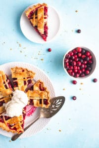 slice pie on a plate with two scoops of ice cream next to a plated slice of pie and a bowl of cranberries