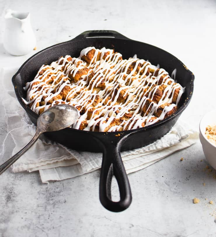 eggnog french toast skillet with a spoon resting against the side and a pitcher in the background