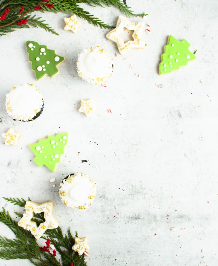 green tree shaped cookies and cupcakes strewn about a concrete surface