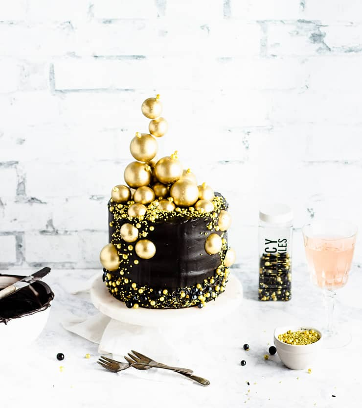 black cake with gold sphere with sprinkles, champagne and a bowl of frosting