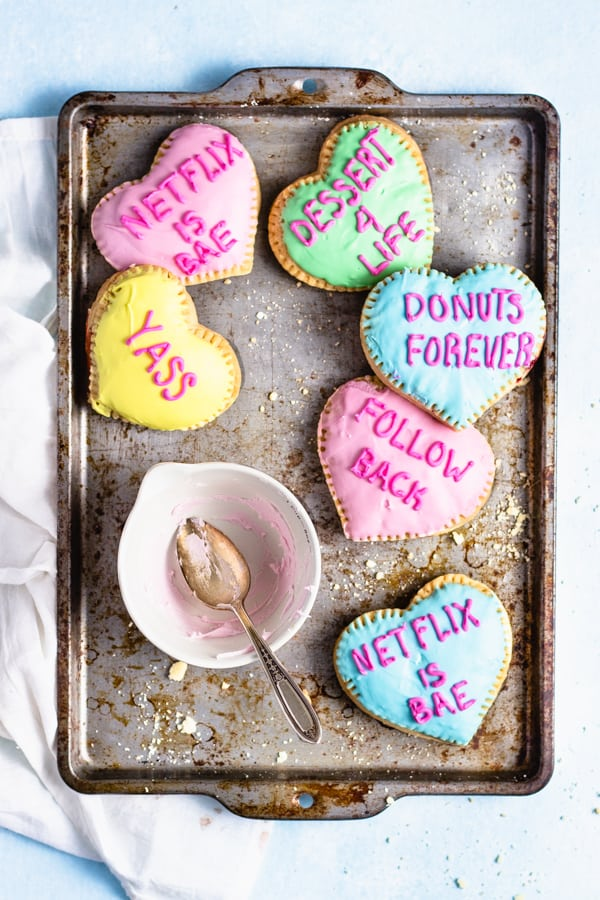 heart shaped pop tarts scattered around a baking tray with an empty bowl of frosting in the middle