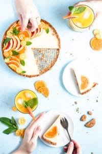 sliced pieces of tart around the larger tart with hands peaking in from the sides to take the plates
