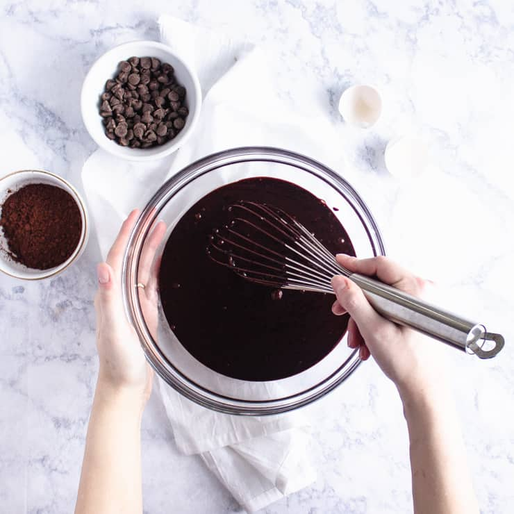 two hands whisking a bowl of chocolate cake batter