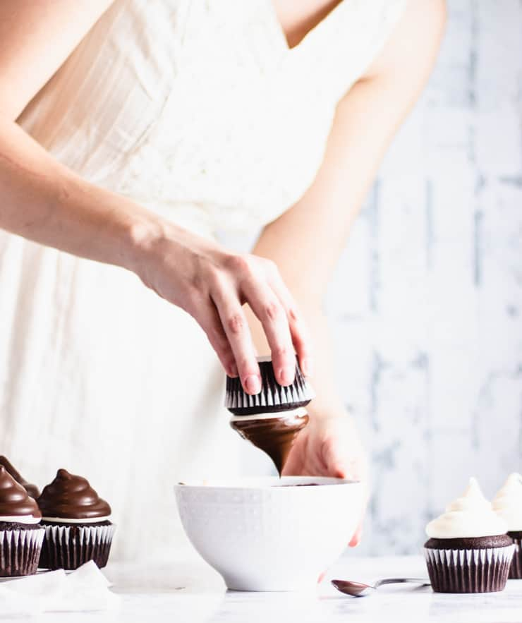 dipping frosted cupcakes into a bowl of melted dark chocolate