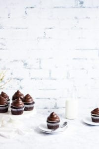 cupcake on a plate next to a cake stand of cupcakes and a bottle of milk