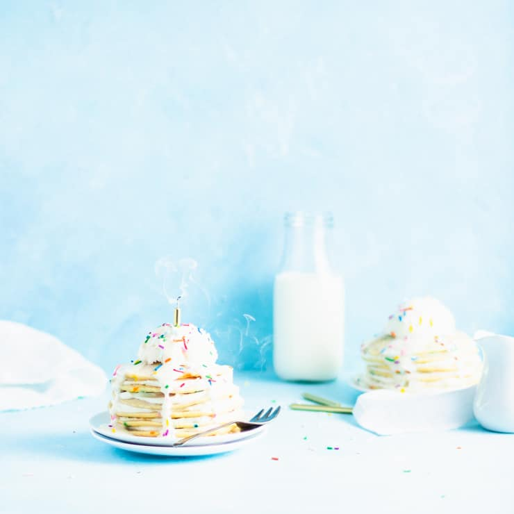 stack of pancakes with a freshly blown out candle and swirling smoke with a glass of milk, sprinkles and another stack of pancakes in the background
