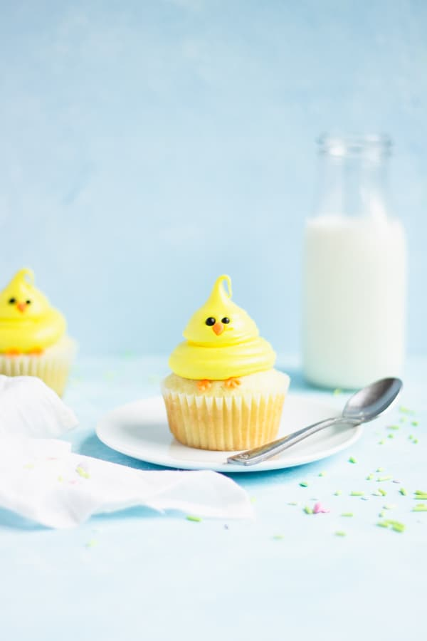 Chick cupcake on a plate with a spoon. A glass of milk is in the background with sprinkles strewn around the sides.