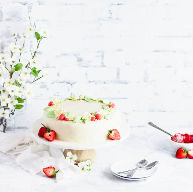 marzipan cake in front of a vase of flowers and a bowl of red jam