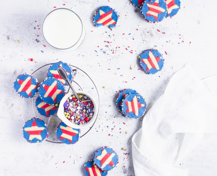 sliced sugar cookies spread around a light backdrop with a glass of milk and a bowl of sprinkles in the middle
