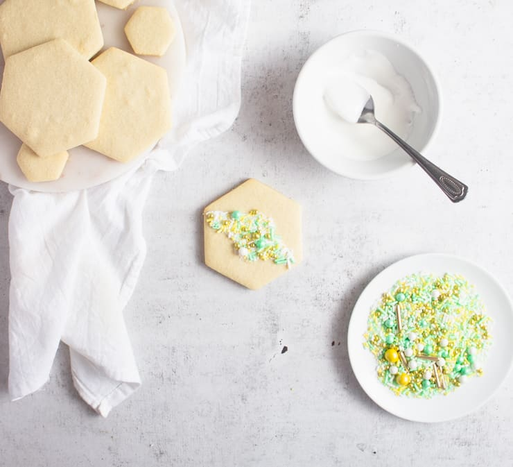 cookie with sprinkles on top and a bowl of royal icing on the side