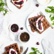 chocolate waffles topped with whipped cream and cherry sauce