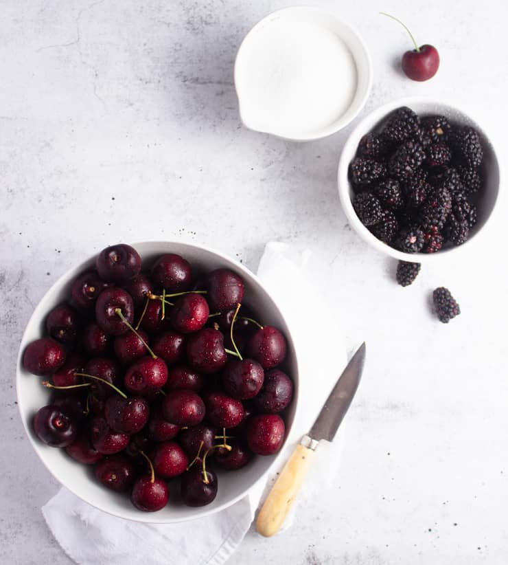 bowl of cherries, bowl of blackberries and bowl of sugar on a white background