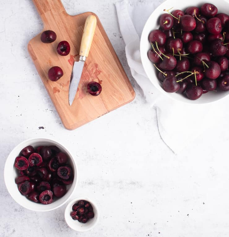bowl of pitted cherries next to a bowl of pits, a cutting board and a bowl of unprocessed cherries