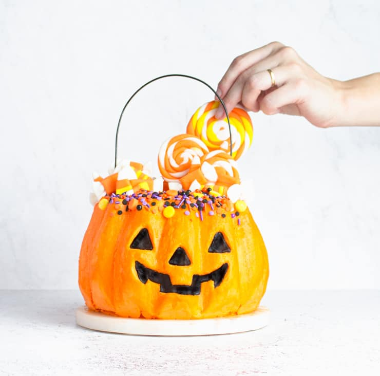 hand placing candy on top of jack-o-lantern cake