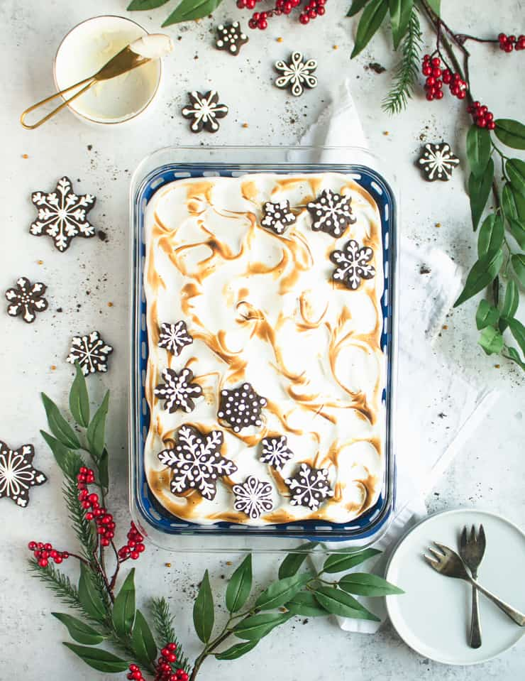 cake with toasted meringue frosting surrounded by cookies and evergreen boughs