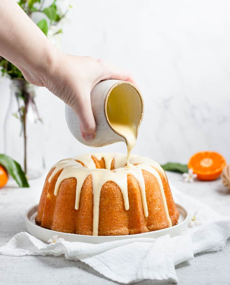 photo of glaze being poured on an orange bundt cake