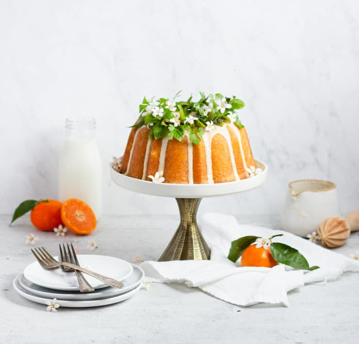 bundt cake on a cake stand with greenery and blossoms on top