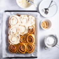 flat lay photo of half frosted cinnamon rolls