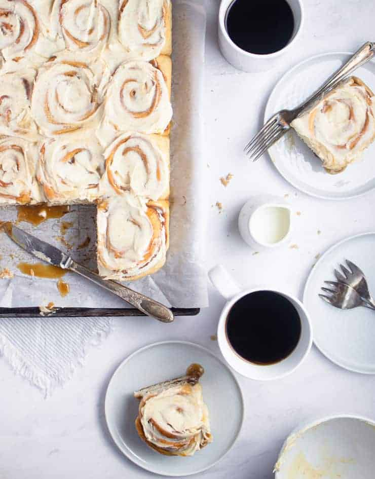 overhead shot of frosted cinnamon rolls next to a cup of coffee