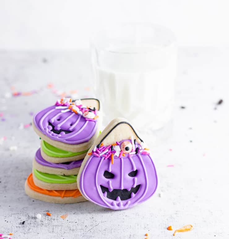 iced cookies stacked next to a glass of milk